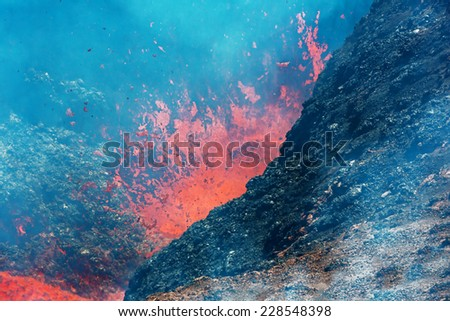 Boiling lava and volcanic bombs in a breakthrough on the slopes of the crater of the volcano Tolbachik - Kamchatka, Russia - stock photo