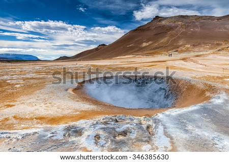 Boiling mudpot in Hverarond geothermal field in Iceland. This is a field in Krafla caldera area near Mvatmn Lake which is full of mudpots, steam vents, sulphur deposits, boiling springs and fumaroles. - stock photo