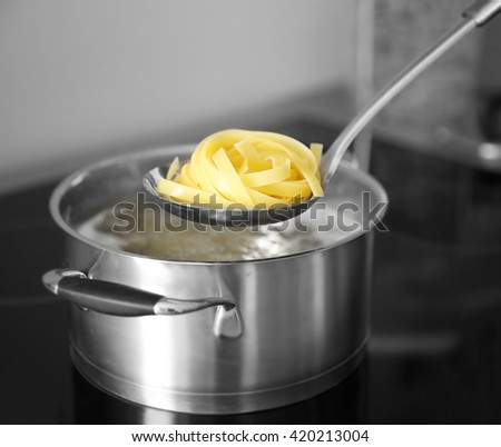 Boiling nest pasta in pan on electric stove in the kitchen - stock photo