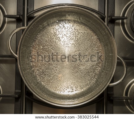 Boiling water for cooking in a metal pan on a stove , cooker