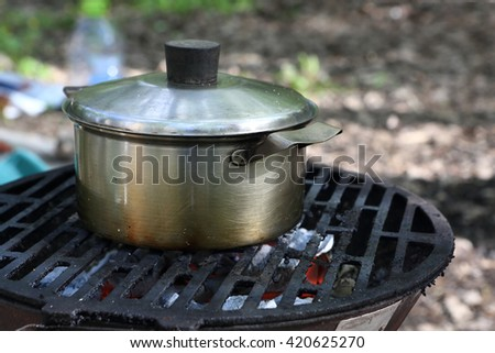 Boiling water in a saucepan on a grill at picnic - stock photo