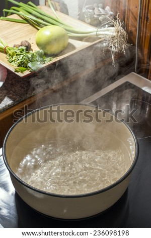 Boiling water in a saucepan. Vintage kitchen - stock photo