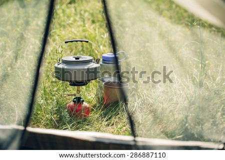 boiling water in titanium kettle on portable camping stove - stock photo