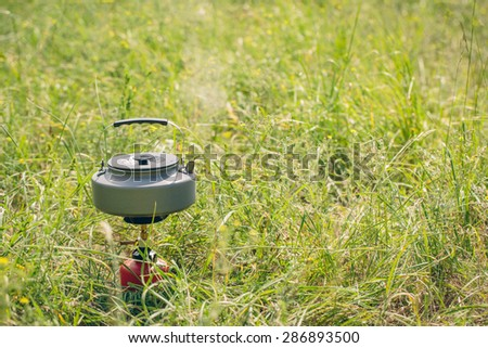 boiling water in titanium kettle on portable camping stove