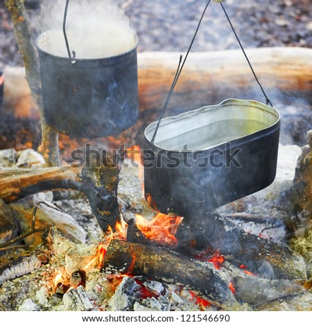 Boiling water in two pots above the fire.