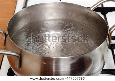 Boiling water into pot on gas stove