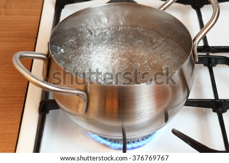Boiling water into saucepan on gas stove