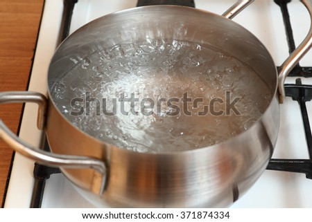 Boiling water on gas stove - stock photo