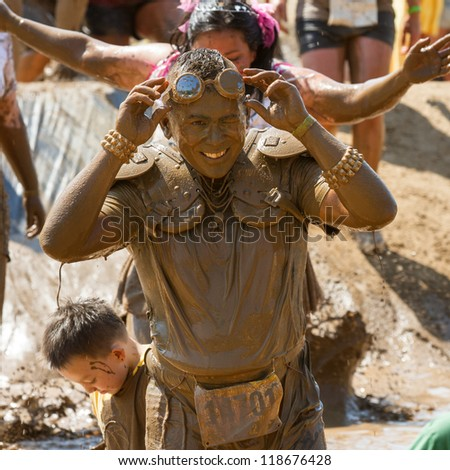 BOISE, IDAHO - AUGUST 25: Runner 14701 lifts his goggles at the Dirty Dash August 25 2012 in Boise, Idaho - stock photo