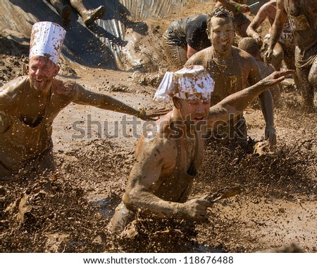 BOISE, IDAHO - AUGUST 25: Runners splash and play in the mud at the Dirty Dash August 25 2012 in Boise, Idaho - stock photo