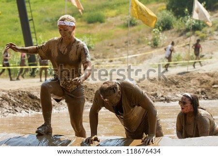 BOISE, IDAHO - AUGUST 25: Runners trying to get over one of the obstacles at the Dirty Dash August 25 2012 in Boise, Idaho - stock photo