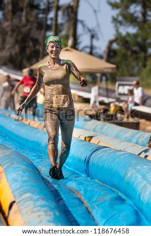 BOISE, IDAHO - AUGUST 25: Unidentified woman runs down the slide at the Dirty Dash August 25 2012 in Boise, Idaho - stock photo