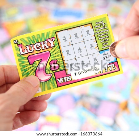 BOISE, IDAHO - DECEMBER 21, 2013: A Lucky 7 scratch ticket being played in hopes of winning a cash prize - stock photo