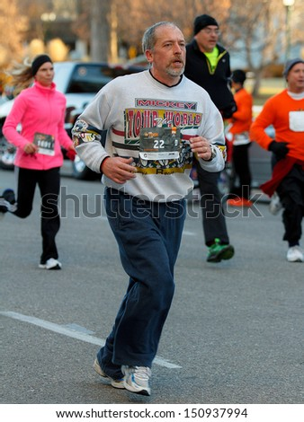 BOISE, IDAHO - NOVEMBER 22:  Man with the bib number 22 runs with a crowd of people during the Turkey Day 5k in Boise, Idaho on November 22, 2012 - stock photo