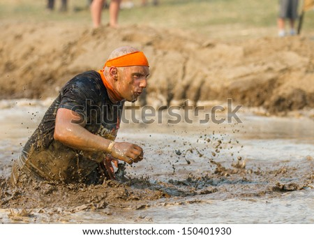 BOISE, IDAHO/USA - AUGUST 10:A man who is unidentified participates by running through the mud pit  at the The Dirty Dash in Boise, Idaho on August 10, 2013  - stock photo