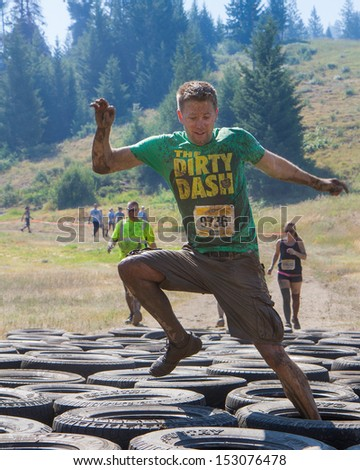 BOISE, IDAHO/USA - AUGUST 10: A runner with bib number 9736 does tries his luck through the tire obstacles at the The Dirty Dash in Boise, Idaho on August 10, 2013  - stock photo