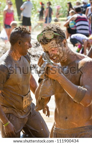BOISE, IDAHO/USA - AUGUST 25:An unidentified man tries to clean up after participating in the Dirty Dash. The Dirty dash is a 10k run through obstacles and mud on August 25, 2012 in Boise, Idaho - stock photo