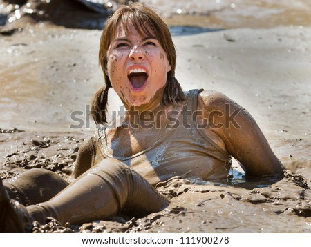 BOISE, IDAHO/USA - AUGUST 25:An unidentified woman sits in a mud puddle shocked expression on her face. The Dirty dash is a 10k run through obstacles and mud on August 25, 2012 in Boise, Idaho - stock photo