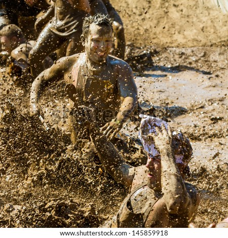 BOISE, IDAHO/USA - AUGUST 25 - Group of people play in the mud making a big splash  The Dirty dash is a 10k run through obstacles and mud on August 25, 2012 in Boise, Idaho - stock photo