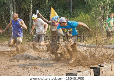 BOISE, IDAHO/USA - AUGUST 10: Group of runners run through the mud mines at the The Dirty Dash in Boise, Idaho on August 10, 2013  - stock photo