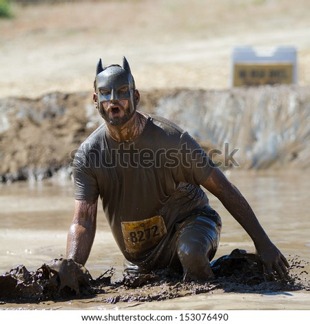 BOISE, IDAHO/USA - AUGUST 10: Man 8272 wearing a batman mask splashes mud at the finish line. This race took place at the The Dirty Dash in Boise, Idaho on August 10, 2013  - stock photo