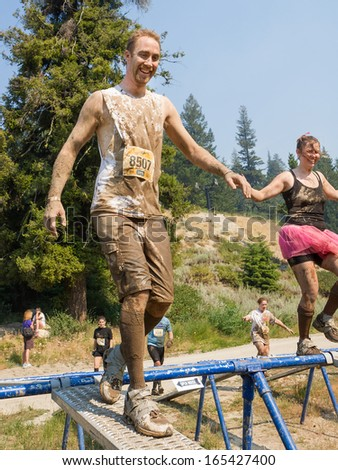 BOISE, IDAHO/USA - AUGUST 10: Runner 8507 goes over the balance beam at the The Dirty Dash in Boise, Idaho on August 10, 2013 - stock photo