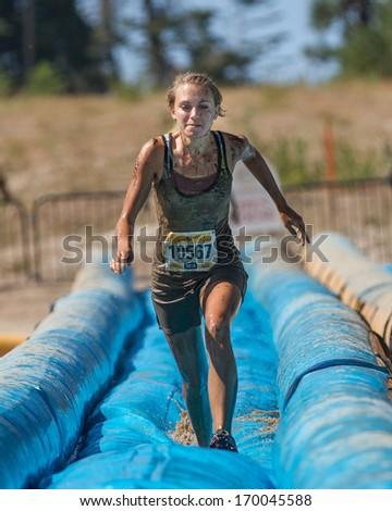 BOISE, IDAHO/USA - AUGUST 10, 2013: Runner 10567 runs fast down the slide at the The Dirty Dash - stock photo