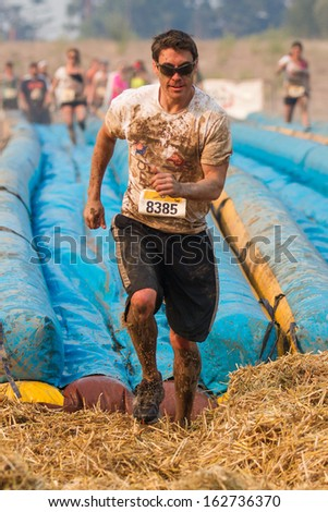 BOISE, IDAHO/USA - AUGUST 10: Runner 8385 runs to the finish at the The Dirty Dash in Boise, Idaho on August 10, 2013  - stock photo