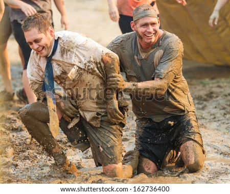 BOISE, IDAHO/USA - AUGUST 10: Two unidentified men horse around and wrestle at the The Dirty Dash in Boise, Idaho on August 10, 2013  - stock photo