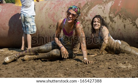 BOISE, IDAHO/USA - AUGUST 10: Two unidentified runners on the ground smiling after falling off an obstacle at the The Dirty Dash in Boise, Idaho on August 10, 2013 - stock photo