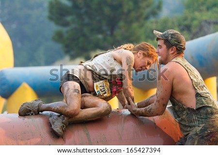 BOISE, IDAHO/USA - AUGUST 10: Unidentified runner being helped over an obstacle at the The Dirty Dash in Boise, Idaho on August 10, 2013 - stock photo