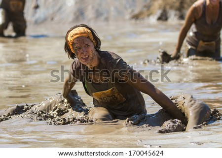BOISE, IDAHO/USA - AUGUST 10, 2013: Unidentified runner makes a splash on her way through the mud at at the The Dirty Dash - stock photo