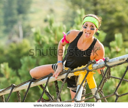BOISE, IDAHO/USA - AUGUST 8, 2014: Unidentified woman climbs over the ropes sticking out her tongue at the Dirty Dash in Boise, Idaho - stock photo