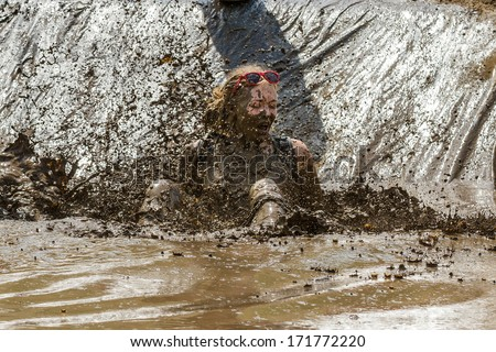 BOISE, IDAHO/USA - AUGUST 11, 2013: Unidentified woman gets a splash of mud thrown her way at the dirty dash - stock photo