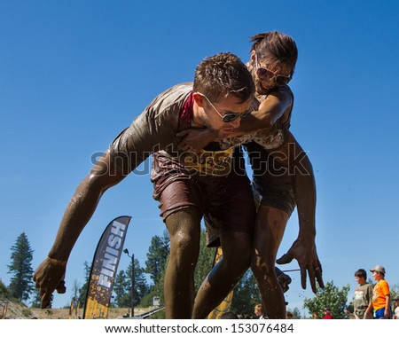 BOISE, IDAHO/USA - AUGUST 10: Unidentified woman is getting off the back of runner 40429 at the The Dirty Dash in Boise, Idaho on August 10, 2013  - stock photo