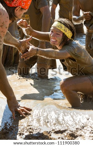 BOISE, IDAHO/USA - AUGUST 25:Unidentified woman is helped up out of the mud during the dirty dash.  The Dirty dash is a 10k run through obstacles and mud on August 25, 2012 in Boise, Idaho - stock photo