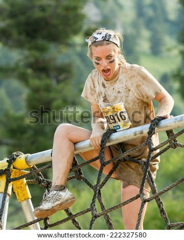 BOISE, IDAHO/USA - AUGUST 8, 2014: Unidentified woman makes her way over the rope climbing at the Dirty Dash in Boise, Idaho - stock photo