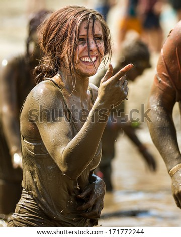 BOISE, IDAHO/USA - AUGUST 11, 2013: Unidentified woman smiles and points near the finish at the dirty dash - stock photo