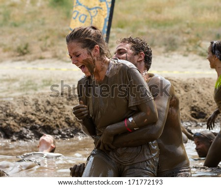BOISE, IDAHO/USA - AUGUST 11, 2013: Woman tries to relax in the mud near the end of the race at the dirty dash