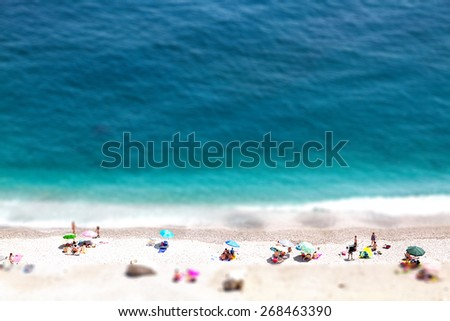 Bokeh effect of high altitude view of beautiful seashore with sunbathe people, vacation and holiday concept, ocean beach view with beautiful waves of clean transparent water and white sand blur effect - stock photo