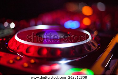 bokeh of DJ turntable and music deck illuminated at night with colourful lights lighting  - stock photo
