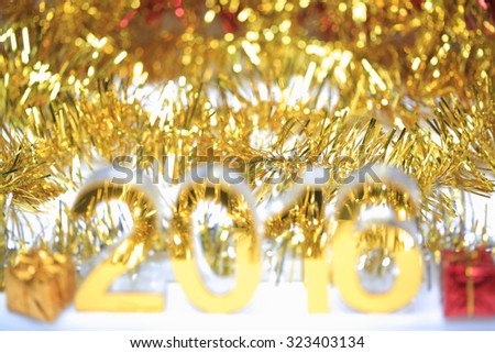 Bokeh of Golden 2016 3d icon with box in the christmas ornaments golden tinsel defocused blur backgrounds - stock photo