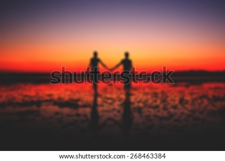 Bokeh Silhouette of young couple in love holding hands at sunset at the seaside, two people in love walking on the beach blur effect - stock photo