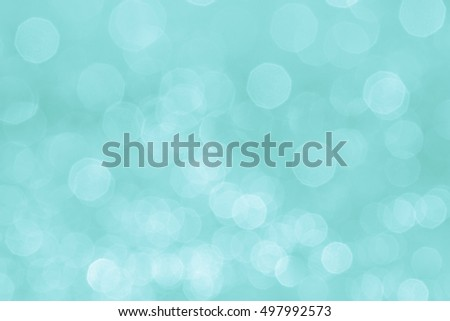 Bokeh soft pastel aqua background with blurred white lights. Festive background.
