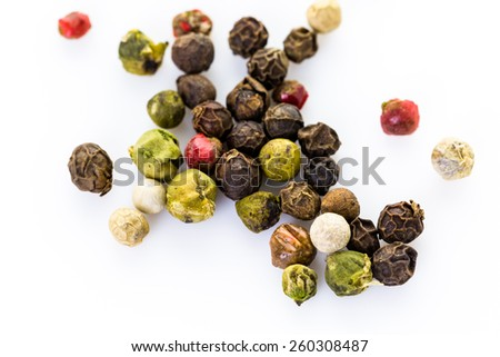 Bold and varied peppercorns on a white background.