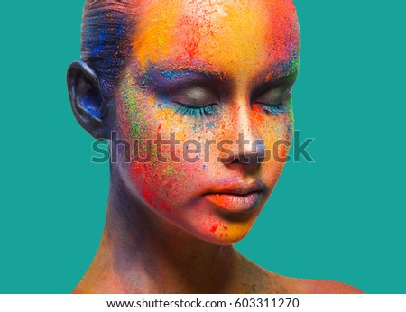 Bold color fantasy. Holi festival of colors background. Female face art with creative make up. Closeup studio portrait of young fashion model with eyes closed isolated on turquoise background