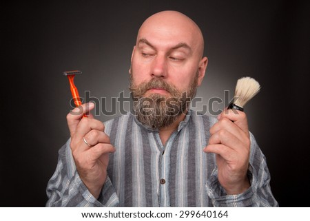 Bold jailbird sitting in the prison isolated on dark grey. Bearded man keeping razor and brush, he is going to shave. - stock photo
