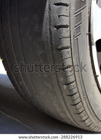 Bold tire with exposed unevenly worn out thread