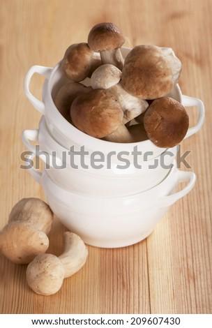 Boletus mushrooms in wicker basket on old wooden table  - stock photo