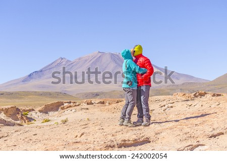 Bolivia, Antiplano - couple of tourists kiss in front of volcano Ollague - stock photo